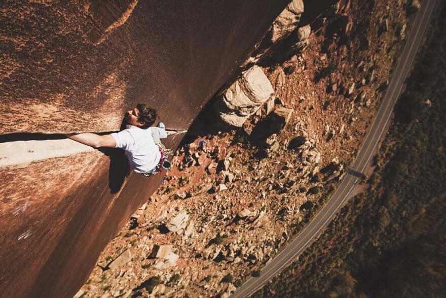 Photo of a rock climbing in the Utah desert.