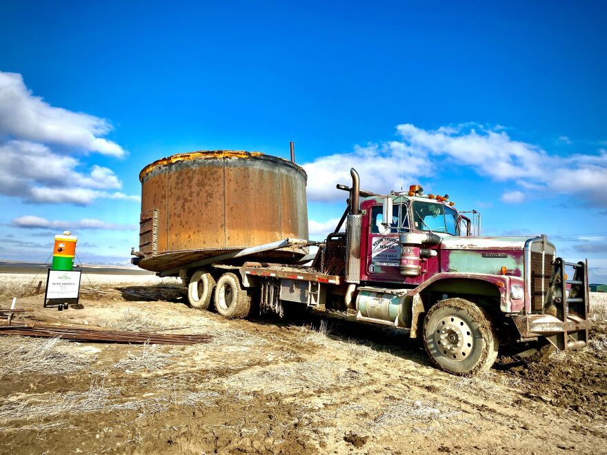 A red semi hauls a large tank over bare earth under a blue sky.