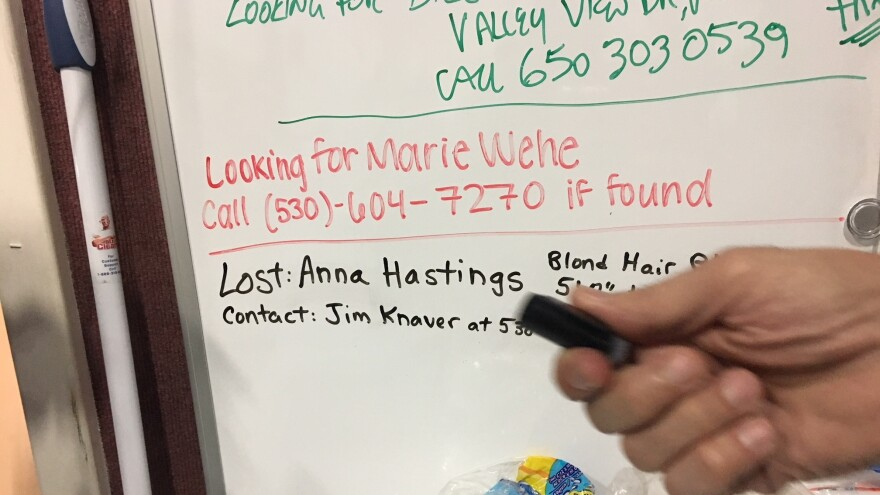 Jim Knaver adds the name of his wife, Anna, to a whiteboard at an evacuation center in Chico, Calif.