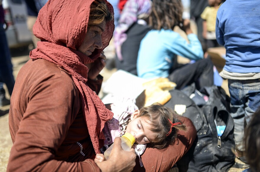 A Syrian Kurd woman gives a bottle to a child Saturday, after they crossed the border between Syria and Turkey.