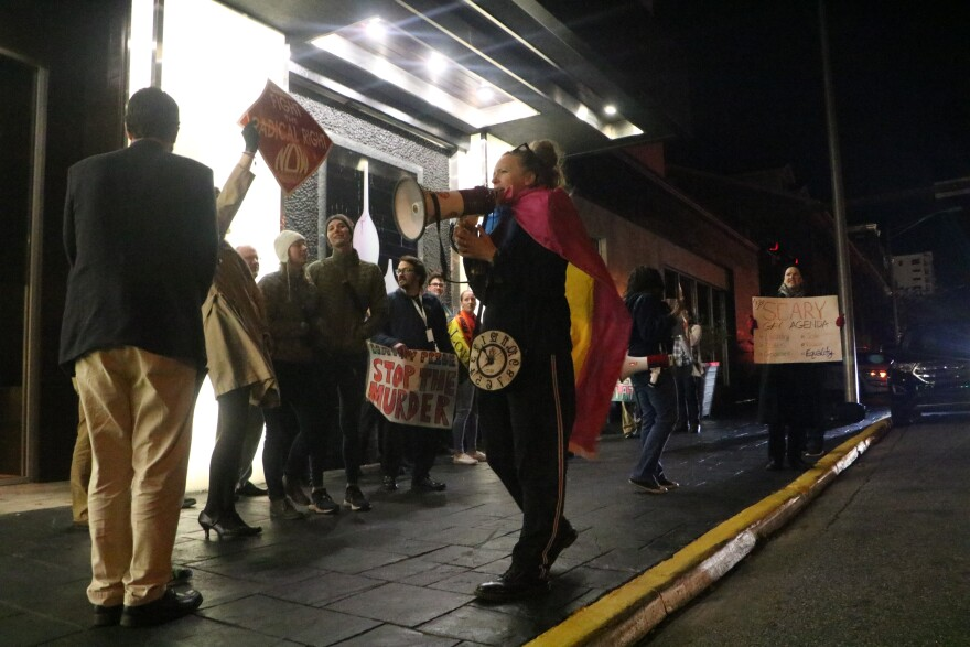 Group of people are screaming on the sidewalk at night. Several people hold up signs. One person screams into a megaphone.