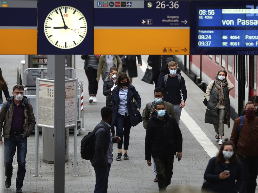 Travelers wear face masks to protect against the spread of the coronavirus at the central station in Munich on Monday. Masks became mandatory in parts of Germany for people shopping and using public transport.