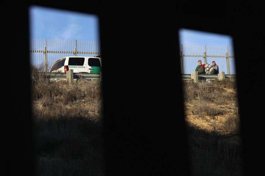 A U.S. Border Patrol agent takes an immigrant into custody in December 2018. Numerous members of the migrant caravan crossed over from Tijuana to San Diego but were quickly taken into custody by U.S. Border Patrol agents.