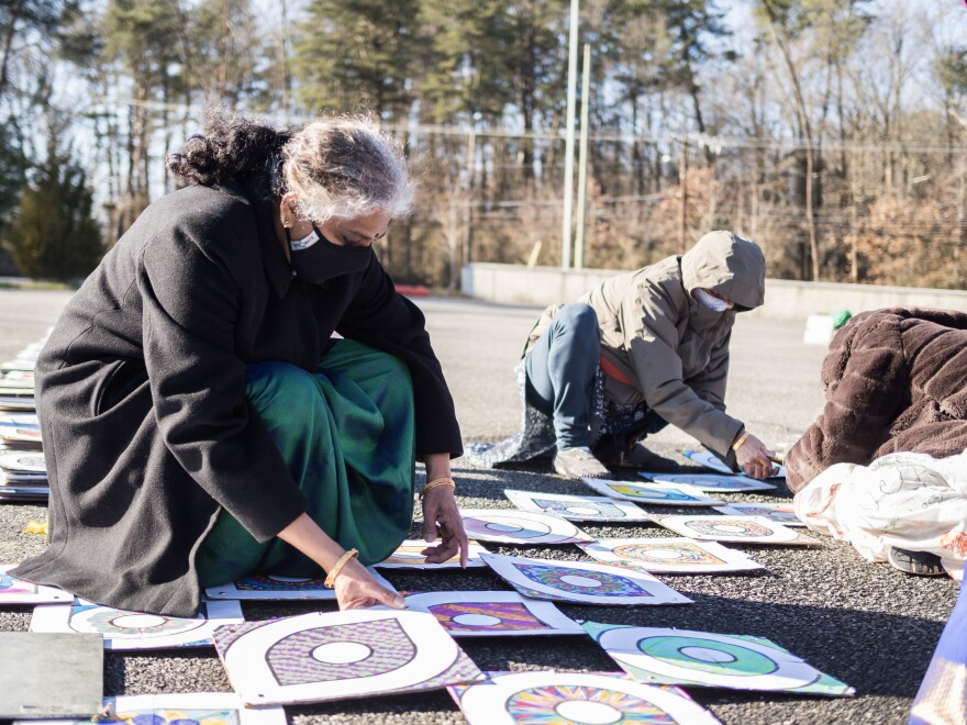 Volunteers assemble a rendition of the inauguration kolam using recycled paper and cardboard. The kolam is a traditional South Indian art form used as a sign of welcome.