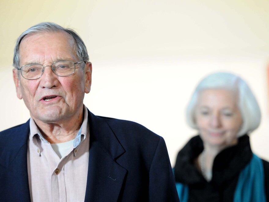 """Korean War veteran Merrill Newman (left), accompanied by his wife, Lee, speaks to the media after arriving at San Francisco International Airport on Dec. 7, 2013, following his release from detention in North Korea. Pyongyang deported Newman after detaining him for two months for """"hostile acts"""" against the communist country."""
