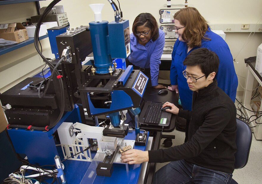 Tahira Reid and Amy Marconnet work with Purdue University graduate student Jaesik Hahn, using an infrared microscope, to study how heat affects hair.