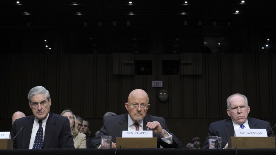 Director of National Intelligence James Clapper (center), accompanied by FBI Director Robert Mueller (left) and CIA Director John Brennan, testifies on Capitol Hill on Tuesday.