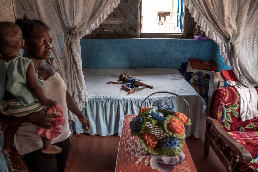 A boy sleeps in a large bed in the spacious home of a successful vanilla farmer in Belambo, Madagascar.