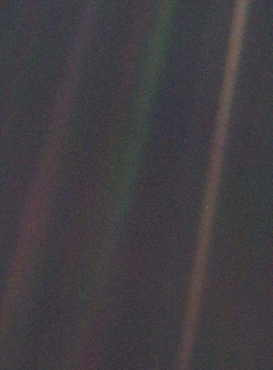 """This color image, known as the """"Pale Blue Dot,"""" is part of the first-ever portrait of the solar system, which was taken by Voyager 1 in 1990. See that tiny dot caught in the middle of the rightmost beam? That's us: all of us."""