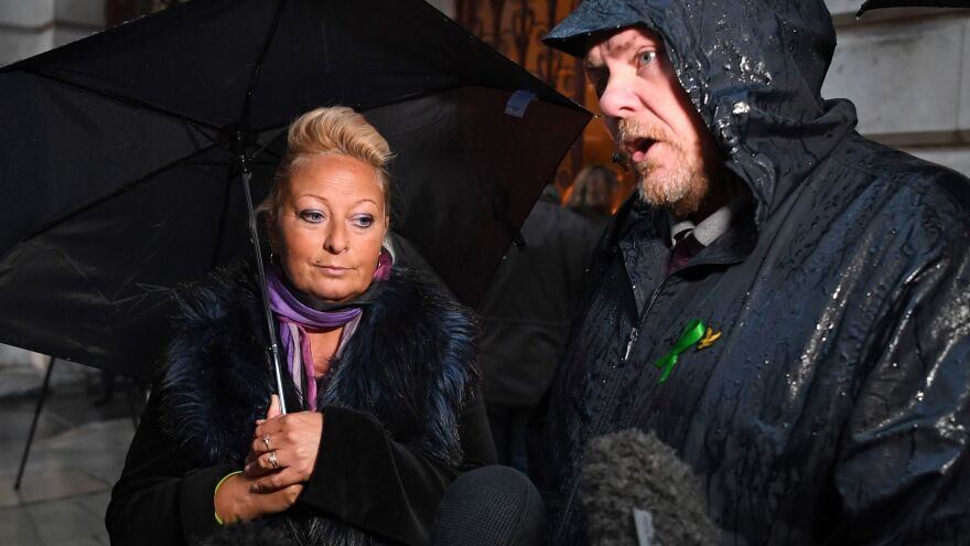Charlotte Charles, the mother of teenage motorcyclist Harry Dunn who was killed in a collision with an SUV driven by U.S. citizen Anne Sacoolas, stands beside her husband Bruce Charles as they discuss the case. Dunn's family is suing Sacoolas, who has claimed diplomatic immunity in the case.
