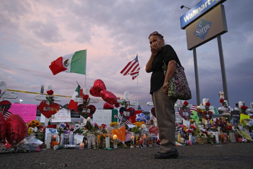 Catalina Saenz wipes tears from her face as she visits a makeshift memorial near the scene of a mass shooting at a shopping complex in El Paso, Texas. A list of the people who died in the weekend shooting rampage at the Walmart, shows that most of the victims had Latino surnames and included one German national.