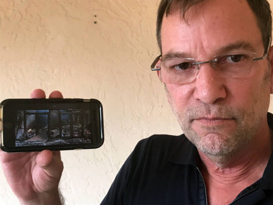 Andrew Bailey, CEO of Anova school, holds a cellphone with a photo of the facility, which was destroyed by the Tubbs Fire this week in Santa Rosa, Calif.