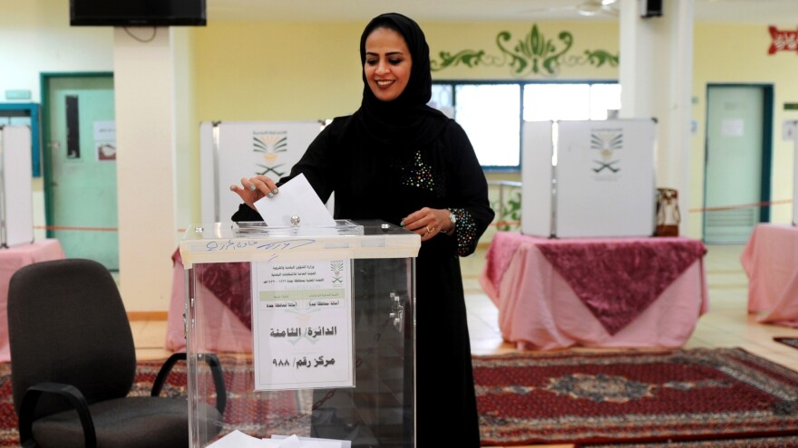 A Saudi woman casts her ballot in a polling station in the coastal city of Jeddah Saturday, as women were allowed to vote in Saudi Arabia's elections for the first time ever.