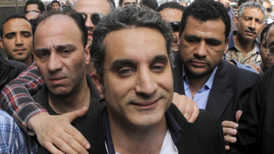 A bodyguard secures popular satirist Bassem Youssef, who has come to be known as Egypt's Jon Stewart, as he enters Egypt's state prosecutors office on Sunday.