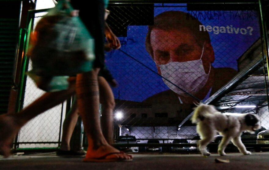 """An image of Brazil's President Jair Bolsonaro wearing a protective face mask and the question, """"Negative?"""" is projected on the wall of a building as a protest against the president regarding his handling of the coronavirus COVID-19 outbreak, in Sao Paulo, Brazil."""