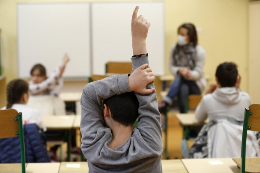 A child raises his fingers to answer his teacher who's wearing a mask. The scene is of a classroom when schools reopened in France in May 2020.