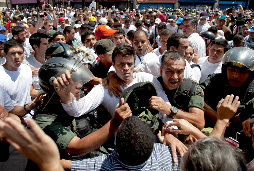 Opposition leader Leopoldo Lopez (dressed in white and holding a flower stem) is taken into custody in Caracas in February 2014. He is being held at a military prison outside the capital. He led protest rallies a year ago. The opposition is currently divided and weak.