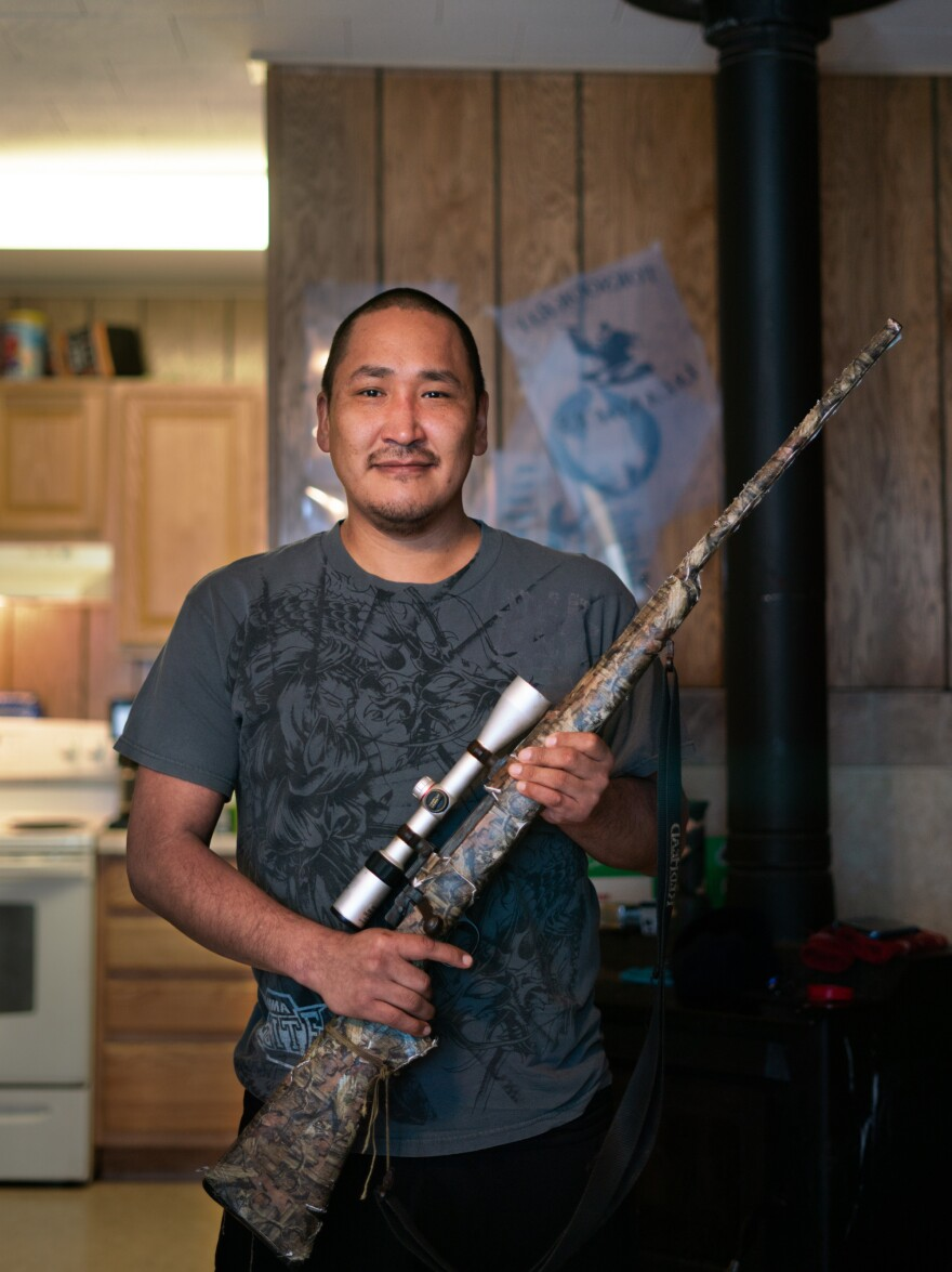 Noah Lincoln holds a gun his family uses for hunting. People in Toksook Bay rely on hunting and other subsistence activities.