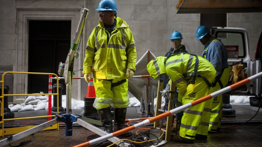 Consolidated Edison workers try to repair damage near the New York Stock Exchange on Tuesday.