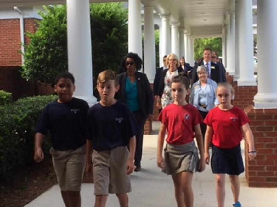 Students lead Education Secretary Betsy DeVos across the campus of Holy Comforter Episcopal School.