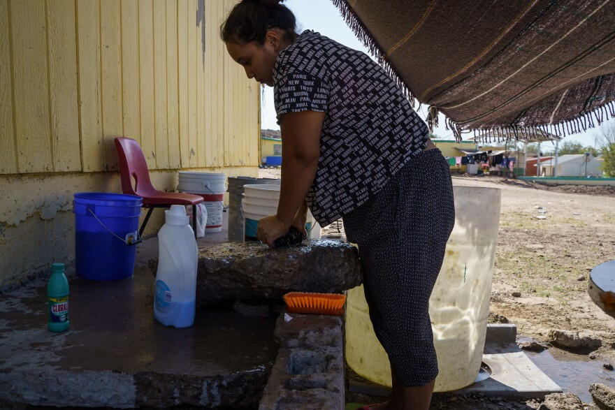 Carolina washes clothes with a stone, soap and bin of water.