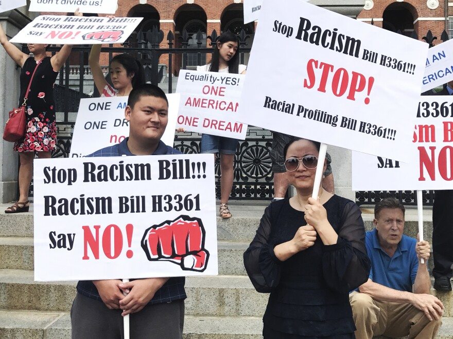 Linglan Zhang (right) of Lexington, Mass., holds a picket sign next to her son, Sean (left), and boyfriend, David Kates (right).