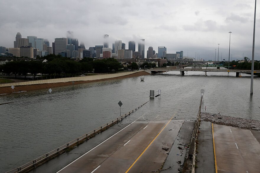 The downtown Houston skyline and flooded Highway 288 are shown on Sunday.