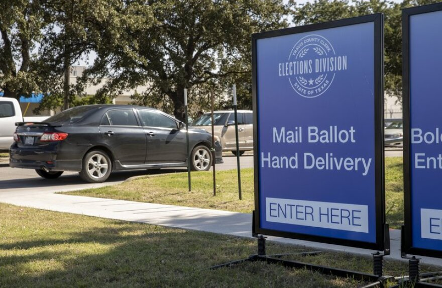 Signs direct traffic at a drive-through ballot drop off location at the Travis County Tax Office in Austin.