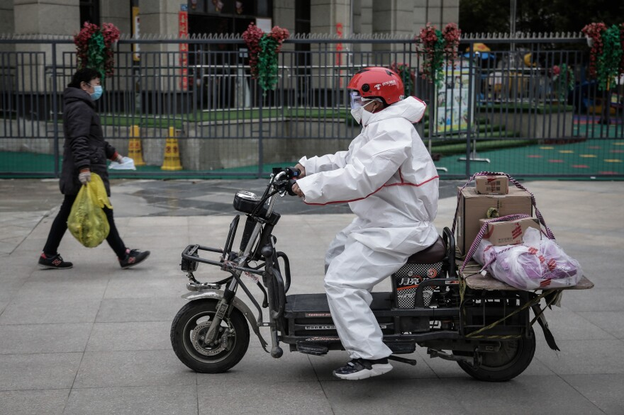 A courier in protective clothing on his scooter. Companies like JD Logistics have been providing masks, protective goggles, gloves and disinfectants to employees. Those who deliver to hospitals are given hazmat suits.