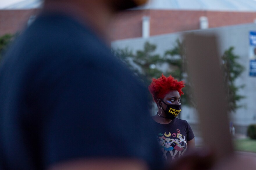 """Kawana Scott, who wears a black mask with the words """"Defund Police"""" in yellow stands outside Dallas City Hall in late August listening to concerns from community members about the upcoming city budget."""