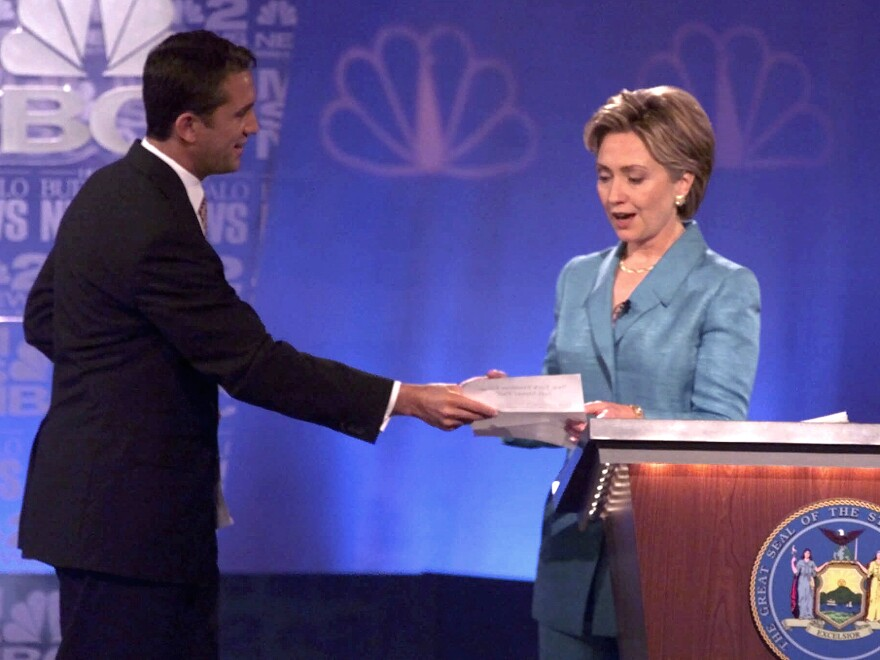 """During a 2000 Senate debate, Hillary Clinton's opponent Rick Lazio, R-N.Y., hands her a pledge to stop taking """"soft money."""" But Lazio's tone was criticized for how not to debate a female candidate."""