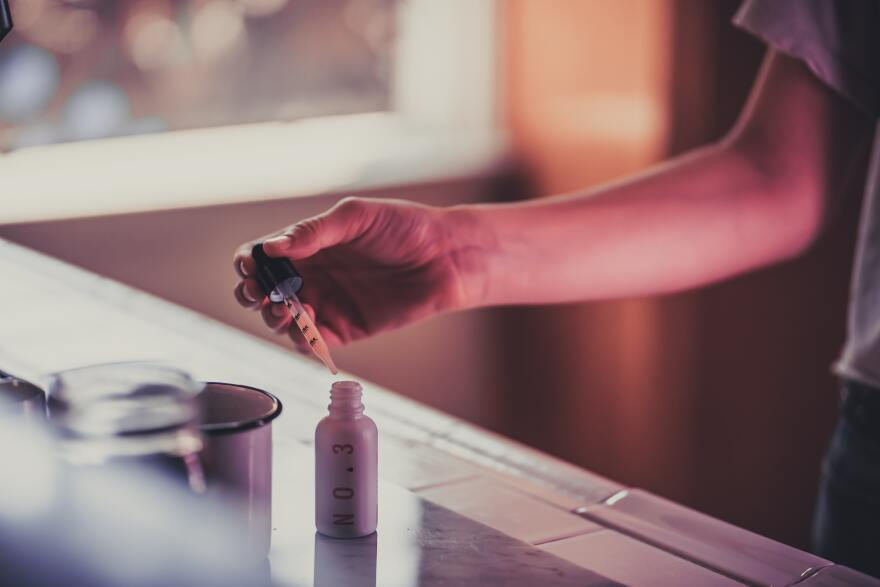 Woman taking few drops of a water-soluble CBD from Eir Health