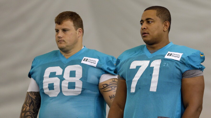 """Miami Dolphins guard Richie Incognito (left) and tackle Jonathan Martin stand on the field during practice in Davie, Fla. Martin left the NFL after he faced harassment from Incognito that his lawyer said went """"beyond locker-room hazing."""""""