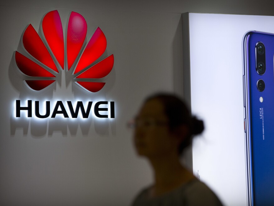 In 2018 file photo, a shopper walks past a Huawei store at a shopping mall in Beijing.