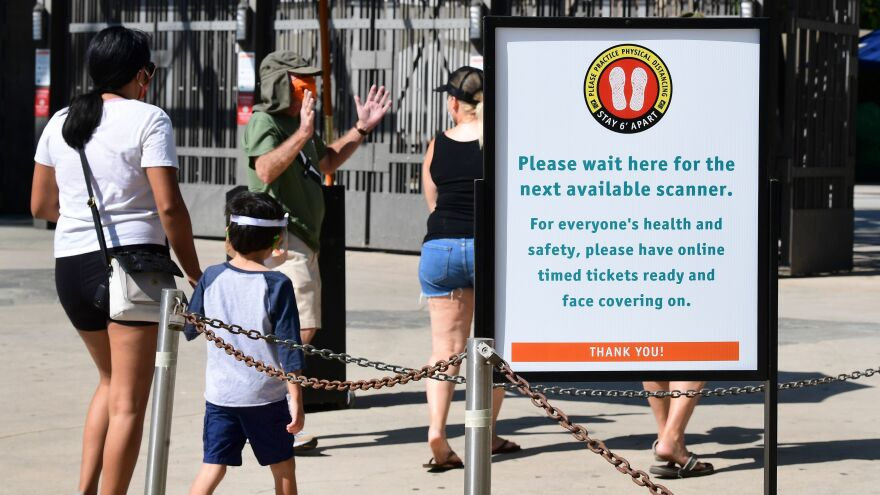 Visitors are reminded of social distancing guidelines while entering the Los Angeles Zoo, which reopened last week after shutting down in mid-March due to the coronavirus pandemic.