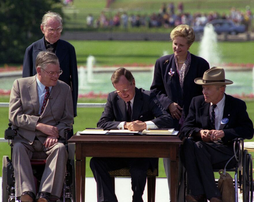 President George H. W. Bush signs the Americans with Disabilities Act on July 26, 1990.