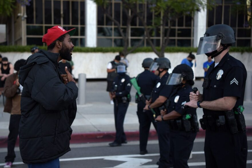 A man reacts in front of a row of police officers as protesters gather in downtown Los Angeles to demonstrate after George Floyd, an unarmed black man, died while being arrested by a police officer in Minneapolis who pinned him to the ground with his knee.