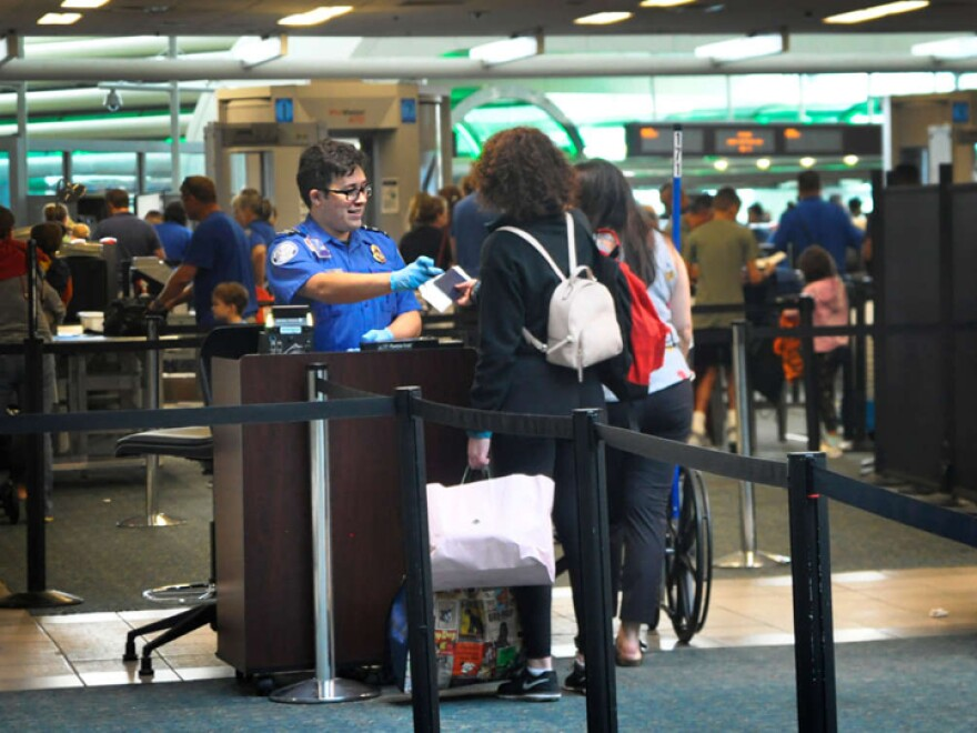 A TSA agent checks identification at Orlando Internantional Airport.