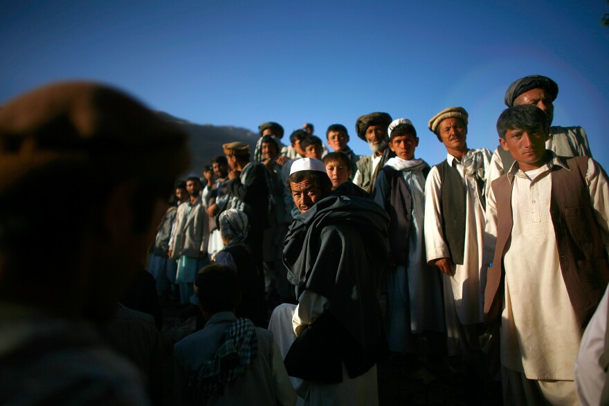 Afghan men assemble for a campaign visit from President Hamid Karzai.