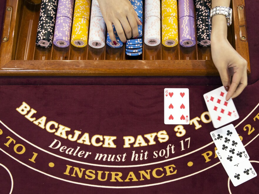 A croupier deals a card on a blackjack table at a Gaming Partners International Corp. (Brent Lewin/Bloomberg via Getty Images)