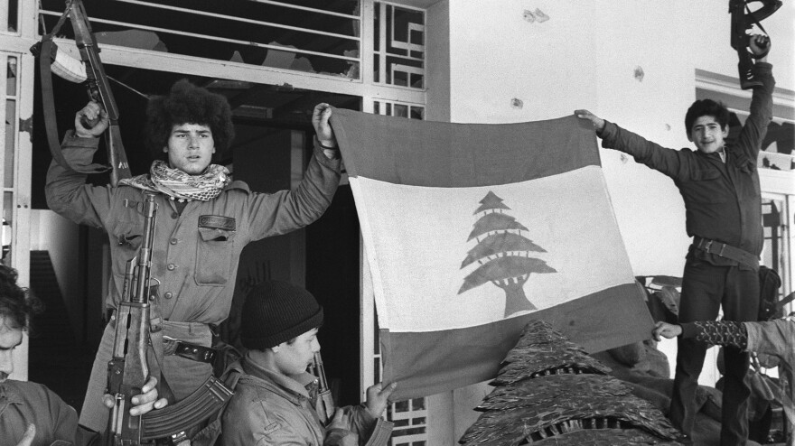 Palestinian fighters unfurl a Lebanese flag at the Holiday Inn after they dislodged Lebanese Christian forces on March 26, 1976. The hotel was a battleground throughout the 1975-'90 Lebanese war, with its upper floors used as snipers' nests.