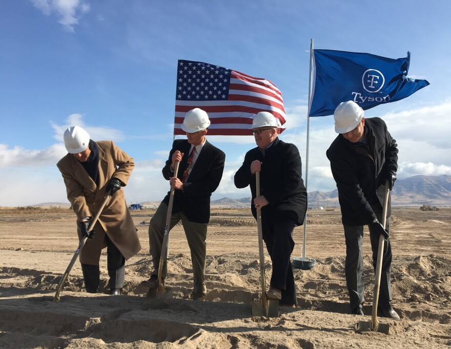 Four men in suits and hard hats shovel dirt for a groundbreaking.