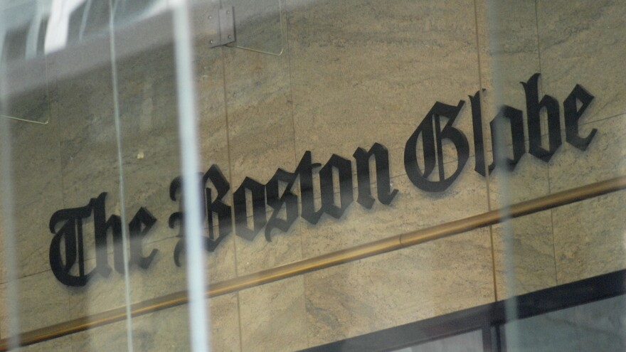 <em>The Boston Globe</em>'s logo as seen through the windows across from the new location of the <em>Globe</em> in Boston. The paper's editors coordinated a campaign defending a free press in editorials.
