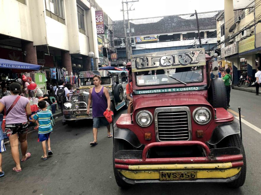 "A jeepney crowned with the name ""Morning Glory"" navigates a Manila street during rush hour. Many jeepneys reach areas of the city where other public transit does not go."