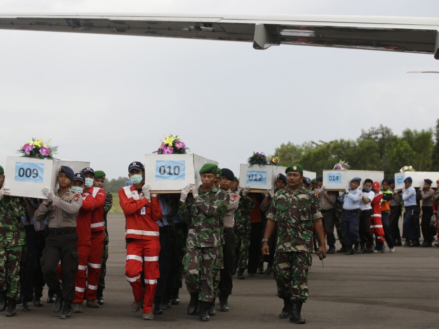 Members of the National Search And Rescue Agency carry coffins containing bodies of the victims aboard AirAsia Flight 8501 to transfer to Surabaya at the airport in Pangkalan Bun, Indonesia, on Friday. Officials say 30 bodies have been recovered so far.