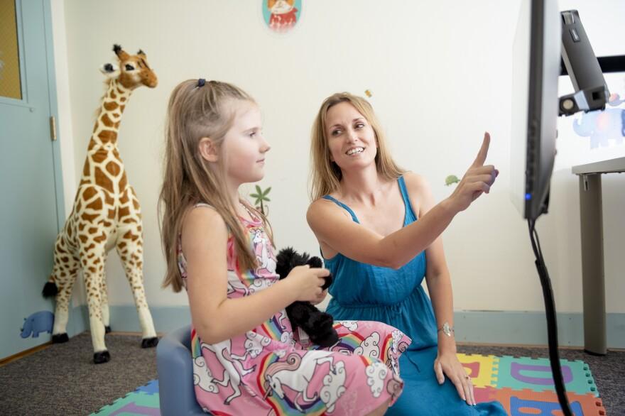 Carnegie Mellon University neuroscientist Jessica Cantlon explains a math game to a participant.