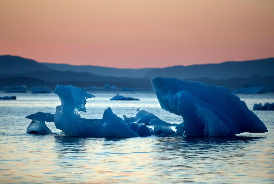 The suns sets as an iceberg floats in the Nuup Kangerlua Fjord near Nuuk in southwestern Greenland, where glaciers have been melting.