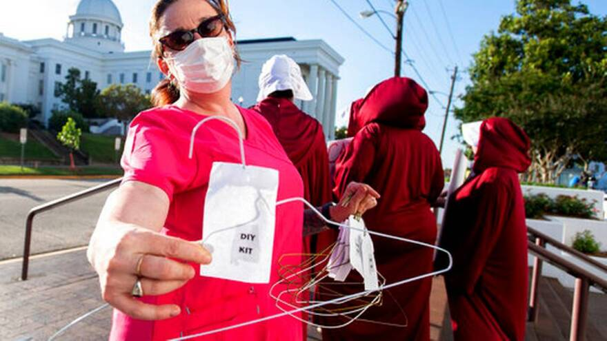 Laura Stiller hands out coat hangers as she talks about illegal abortions during a rally against a ban on nearly all abortions outside of the Alabama State House in Montgomery, Ala., on Tuesday, May 14, 2019.