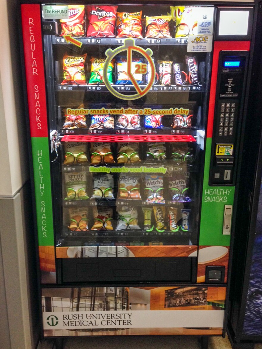 "A vending machine with the DISC, or ""Delays to Influence Snack Choice,"" installed.  On the display window, a written decal tells customers they'll have to wait for an extra 25 seconds for unhealthy snacks.<strong></strong>"