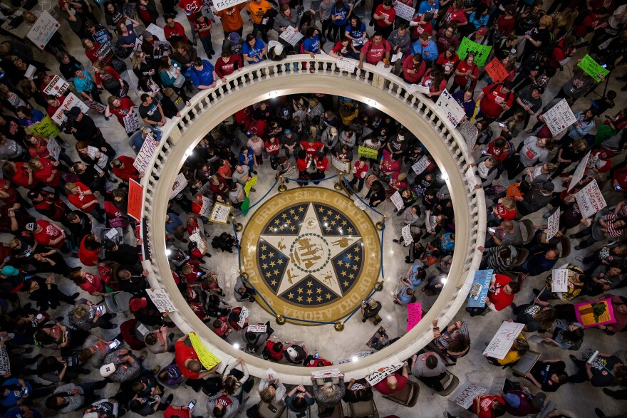 Teachers and demonstrators hold signs during a rally inside the Oklahoma State Capitol building in Oklahoma City, Okla. Hundreds of teachers gathered to press demands for additional funding for the state's public schools.